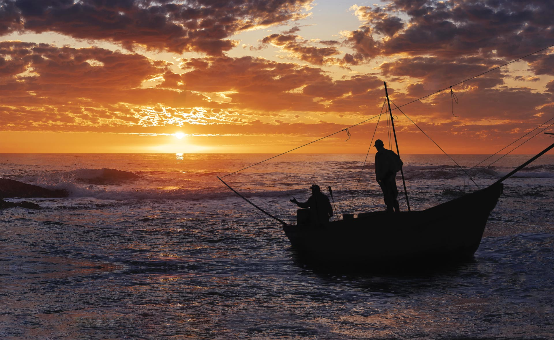 fishermen on boat with sunset
